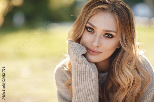 Fototapeta premium Moda jesień portret kobiety z żółtymi liśćmi klonu na tle przyrody. Ładna kobieta spaceru w parku i ciesząc się piękną przyrodą. Piękna młoda szczęśliwa dziewczyna z jaskrawym czerwono-żółtym liściem w parku