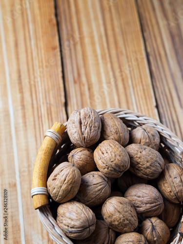 Fotomural  Walnut on a wooden table in a wicker basket