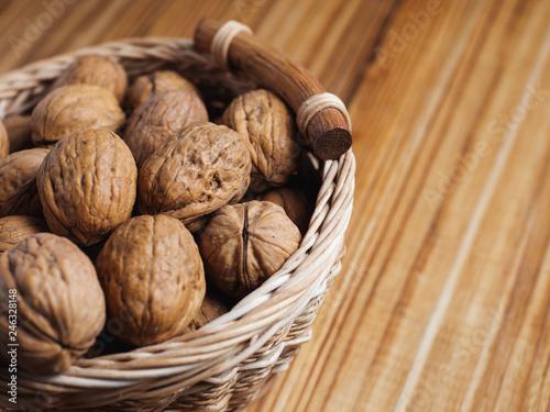 Pinturas sobre lienzo  Walnut on a wooden table in a wicker basket