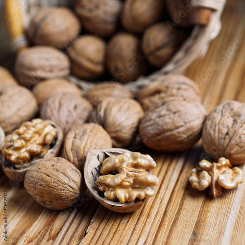 Fotografía  Walnut on a wooden table in a wicker basket