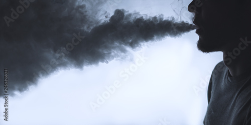 Fototapety, obrazy: Vaping man. Close-up of a man with a beard releases a cloud of steam