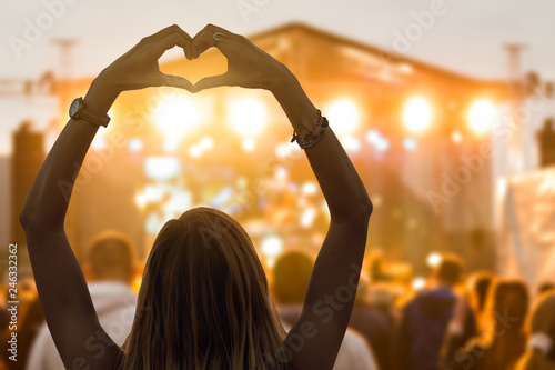 Girl with heart-shape symbol enjoying her favorite group on the concert. - 246332362
