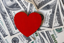 Red Heart And One Hundred Dollar Money Dollars With The Image Of Franklin Scattered On The Surface