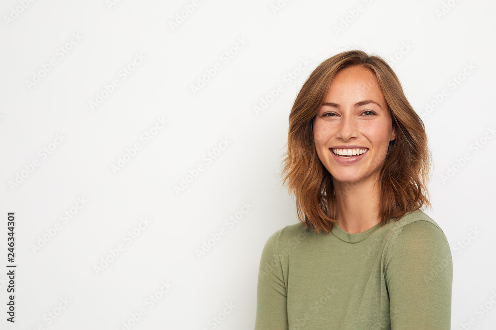 Fototapeta portrait of a young happy woman smiling on white background