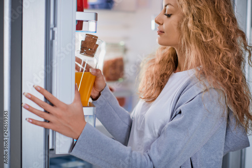 Side view of beautiful Caucasian woman with curly hair taking juice in glass bottle from fridge.
