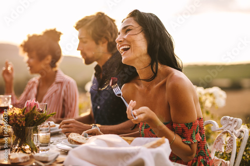 Woman enjoying with friends at outdoor dinner party - 246363339