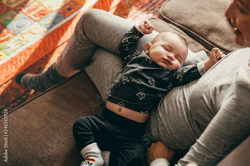Photo Top view of a baby sleeping in the lap of his mother