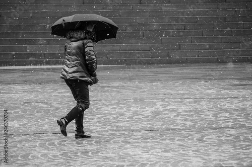 obraz dibond Portrait of woman walking with umbrella and winter coat by snowy day on cobbles place