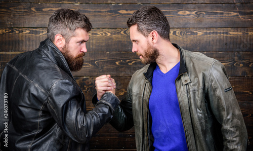 Fényképezés  Brutal bearded men wear leather jackets shaking hands