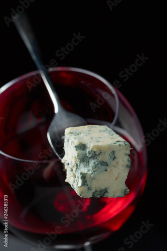 Piece of blue cheese on a fork and a glass of red wine.