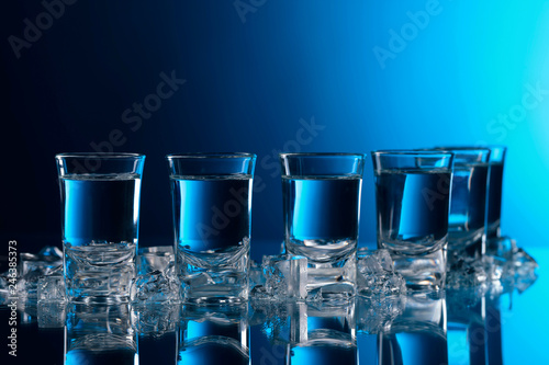 Glasses of vodka with ice on a glass table.