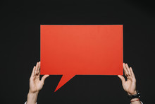 Cropped View Of Man Holding Red Speech Bubble In Hands Isolated On Black