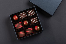 Assortment Of Luxury Bonbons With Red Splashes In Box On Black Background