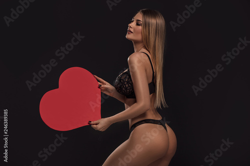 Sexy woman in lingerie holding red heart.