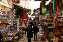 Some People Walk Through The Streets Of The Old City Of Jerusalem With Stalls And Shops Selling Souvenirs And Food.
