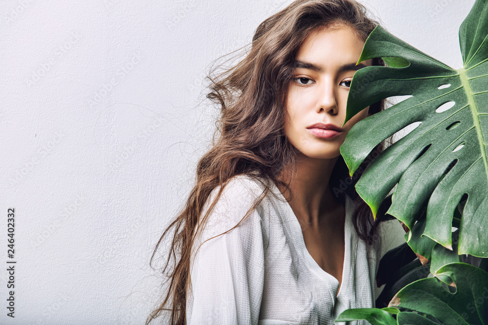 Fototapety, obrazy: Young beautiful girl model Asian brunette with long hair posing in Studio with tropical plant on isolated background