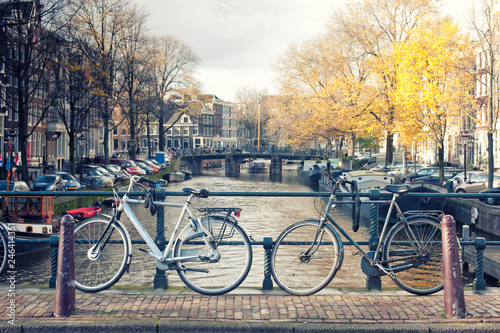 Foto op Canvas Kanaal Bicycles lining a bridge over the canals of Amsterdam, Netherlands in vintage style.