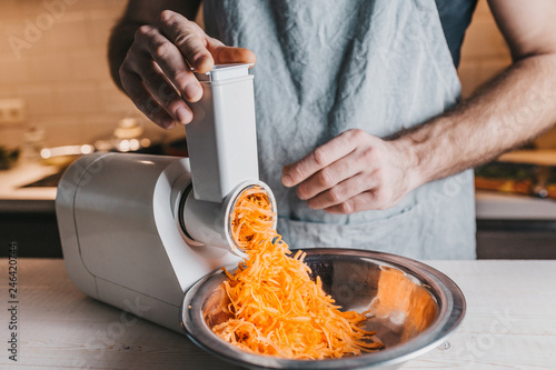Photographie Closeup of a rough male chef hands chopping carrots on an electric meat grinder