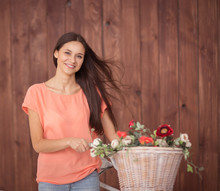 Young Woman With A Bicycle Carrying A Beautiful Basket Full Of Flowers