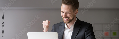 Fotografiet  Horizontal photo happy businessman in suit sitting at desk look at laptop read r