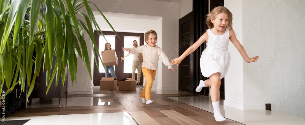Fototapeta Horizontal photo happy little kids running into new home, parents with cardboard boxes on background. Loan mortgage, moving relocating concept banner for website header design with copy space for text
