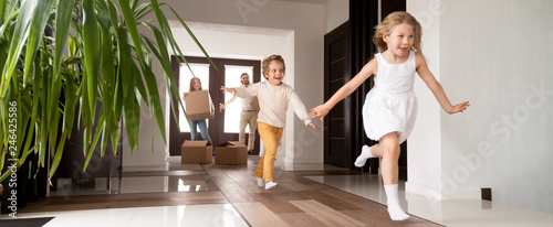 Fototapeta Horizontal photo happy little kids running into new home, parents with cardboard boxes on background. Loan mortgage, moving relocating concept banner for website header design with copy space for text obraz