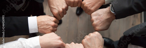 Fotografía  Top above close up view group of businessmen in formal suits standing putting hands fists in circle shape