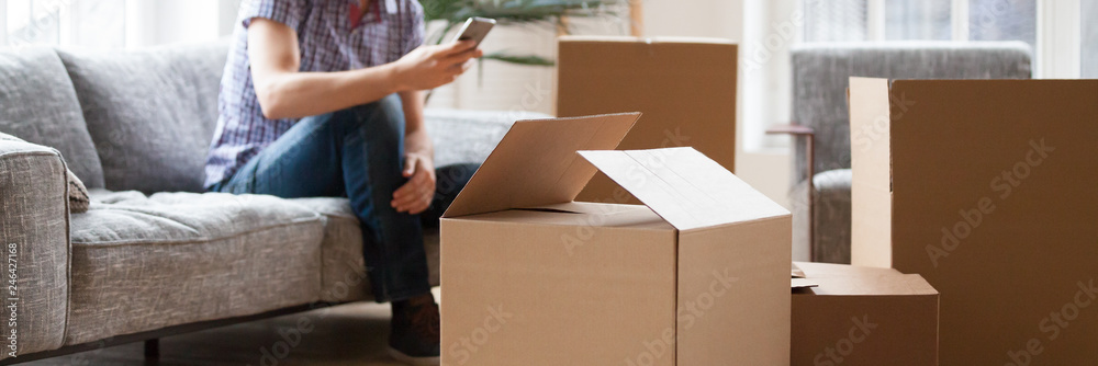 Fototapeta Close up carton boxes with belongings man sitting on sofa hold phone on background, wait call to delivery service moving at new house concept, banner for website header design with copy space for text