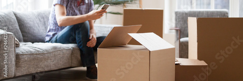 Photo Close up carton boxes with belongings man sitting on sofa hold phone on backgrou