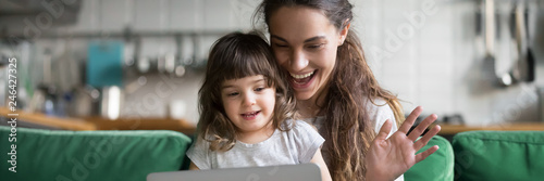 Mixed race mother and daughter using computer make video call waving hands greeting friend, having fun online modern tech applications concept banner for website header design with copy space for text