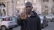 Young american african guy in street making no with finger.Negativity,refusal