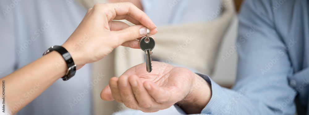 Fototapeta Horizontal photo reliable real estate agent giving keys to senior couple, male female hands close up, spouses buying new home receive loan mortgage investing concept, banner for website header design
