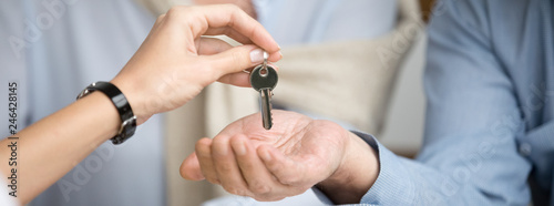Horizontal photo reliable real estate agent giving keys to senior couple, male female hands close up, spouses buying new home receive loan mortgage investing concept, banner for website header design