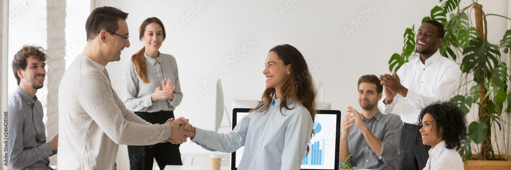 Fototapeta Boss welcoming new employee hired intern female, mixed race woman feel happy promoted receive appreciation for good work result from company head colleagues applauding banner for website header design