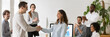 canvas print picture - Boss welcoming new employee hired intern female, mixed race woman feel happy promoted receive appreciation for good work result from company head colleagues applauding banner for website header design