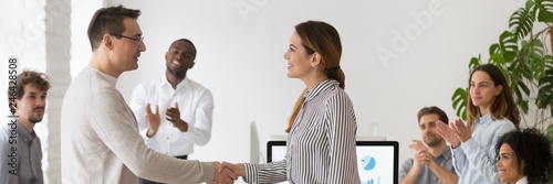 Photo Boss handshaking with promoted female worker congratulating with success showing appreciation with good work result diverse colleagues clapping hands