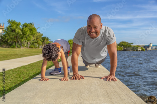Valokuva  A father smiles as he shows his young son how to do pushups on the seawall at the intercoastal