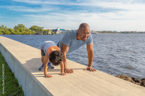 A father is showing his young son how to do pushups on the