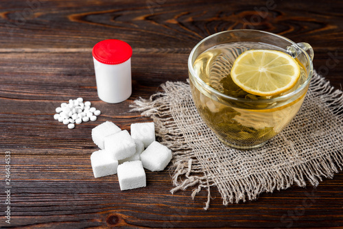 Sweetener or sugar and green tea with lemon on wooden background. Canvas Print