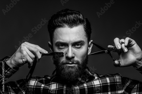 Fotografía  Handsome bearded young man in a plaid shirt holding a sharp professional scissors and razor isolated on dark background