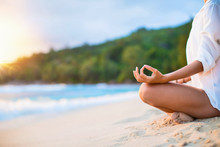 Closeup Of Woman's Practicing Lotus Pose On The Beach At Sunset