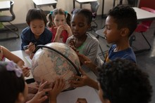 Group Of Kids Studying A Globe...