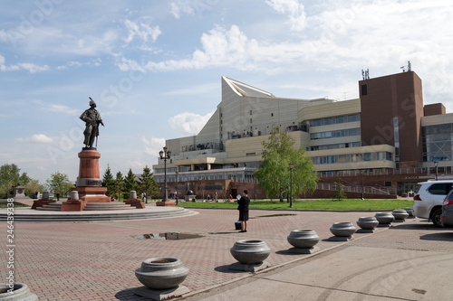 In de dag Theater woman photographs a monument to statesman N.P. Rezanov on the square in front of the Great Concert Hall in the city of Krasnoyarsk. Russia.