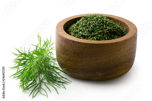Fotografía Dried chopped dill in a dark wood bowl next to fresh dill leaves isolated on white