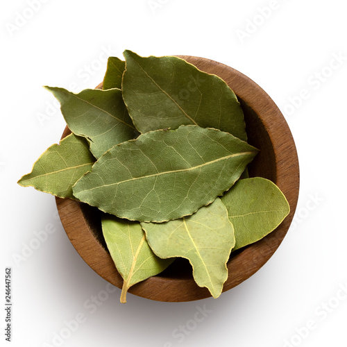 Canvas-taulu Dried bay leaves in a dark wood bowl isolated on white from above