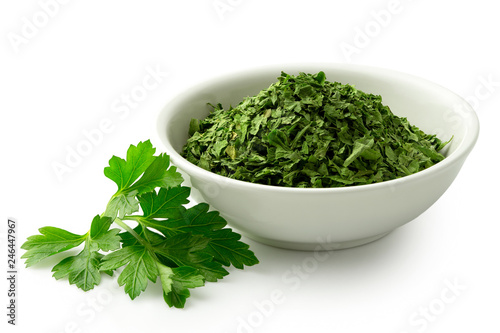 Fotomural Dried chopped parsley in white ceramic bowl next to fresh parsley leaves isolated on white