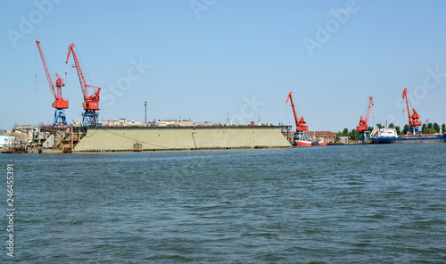 Fotobehang Poort Portal cranes and floating ship dock from the sea. Kaliningrad region