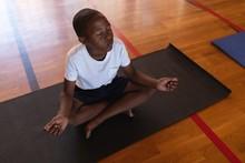 Schoolboy Doing Yoga And Meditating On A Yoga Mat In School