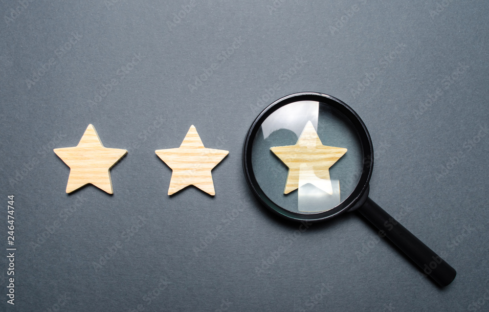 Fototapeta Three stars and a magnifying glass on a gray background. Authentication of the third star, rating fraud. Rating and status of the restaurant or hotel. Prestige.. High quality and reliability