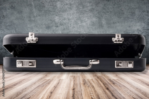Photo ajar black modern case on a laminate floor on a concrete wall background